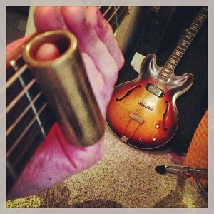 Brass slide on Guild guitar neck with mid-60's Gibson 125 on the floor.
